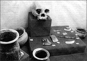 Black-and-white reproduced photo of Huluga female cranium and artifacts. Courtesy of Museo de Oro.
